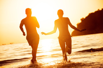 Happy couple run to sunset sea