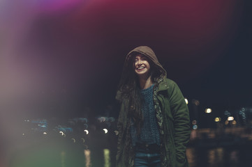 Joyful young woman laughing and walking in a promenade with city lights bokeh on backgorund