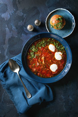 Plate of traditional beetroot borscht soup with sour cream and fresh coriander served with garlic bread buns pampushka with blue textile over dark blue texture background. Top view, space