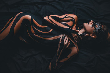 Beautiful girl with painted body and black mask in her face lies on bed. Body art.