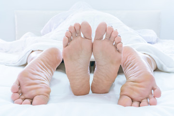 Couples feet sticking out from under DUVET or BLANKET make love at home on bedroom.