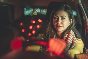 Young attractive woman driving at night in a traffic jam with city lights bokeh on background