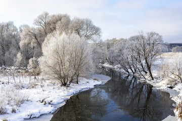 Beautiful winter landscape with forest, river and blue sky. A cold winter day.
