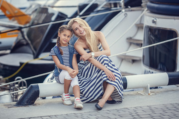 The elder sister and younger sisters and a brother in a marine style against the backdrop of boats and yachts. Idea and concept Friendship, vacation, vacation, family