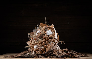 Bouquet of brown nuts on wood background in a paper wrapper