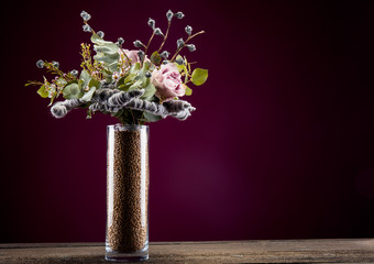 Original and unusual bouquet in a glass vase on a wooden background
