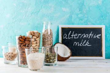 Vegan alternative food, set of various ingredients for non-dairy milk - rice, coconut, almonds, pistachio, sesame, pumpkin seeds, soy, nuts, oatmeal, on light blue background, copy space