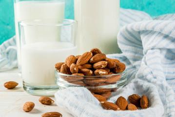 Vegan alternative food, almond non-dairy milk on light blue background, copy space