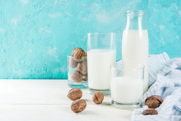 Vegan alternative food, walnut non-dairy milk on light blue background, copy space