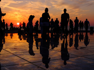 People having fun during a great sunset in Zara with reflections