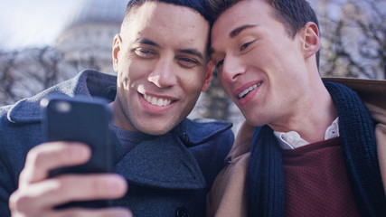 Happy young male couple smiling as they look at something on a phone together