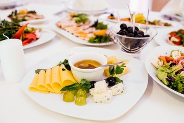 Photo of cheese platter and salad on the table
