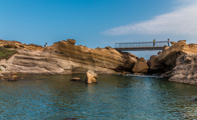 Scenic view of the Lion's Head Rock inside the pond. In the background, the beautiful sandstone layers can be admired and visitors are taking photos on the footbridge at Yehliu Geopark, Taiwan.