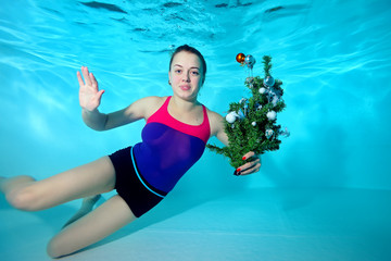 Cute young coach-girl swims underwater in the pool with the toy in his hand and looking at the camera. Portrait. Horizontal orientation. A view from under the water