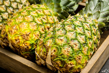 Fresh ripe pineapples on the rustic background. Selective focus.