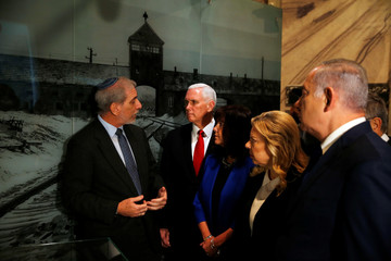 U.S. Vice President Mike Pence, his wife Karen, Israeli Prime Minister Benjamin Netanyahu and his wife Sara listen to a guide as they visit the Yad Vashem Holocaust History Museum in Jerusalem