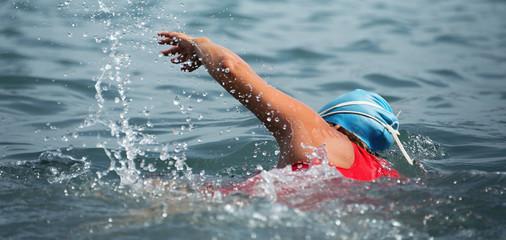 Woman swimmer swimming crawl in blue sea,training for triathlon