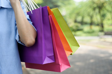 Asian woman holding shopping bags while walking in the park.
