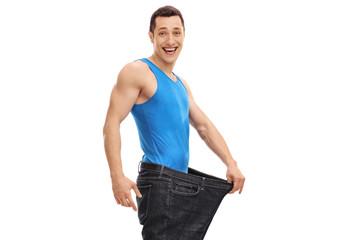 Joyful man wearing a pair of oversized jeans