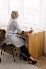Young female doctor working desk in doctor's room writing.
