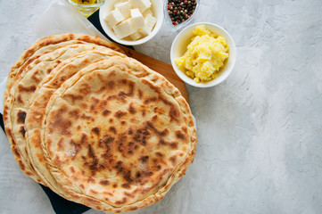 Mashed potato and sheep cheese filling flatbread on a white stone background.