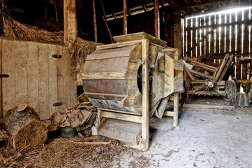 Old wooden threshing machine standing in an old barn