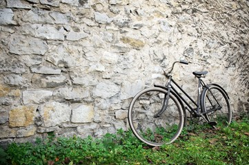 Old bike standing on grass in front of old stone wall