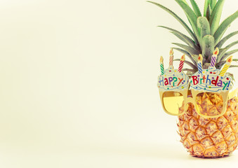 yellow fancy glasses on fresh pineapple, copy space on left, summer birthday concept, pastel color tone