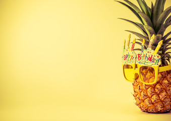 yellow fancy glasses on fresh pineapple, copy space on left, summer birthday concept, retro color tone