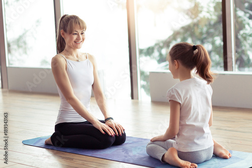 Young mother and little kid daughter in the gym centre doing