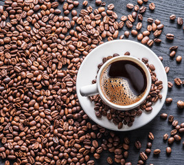 Cup of coffee surrounded by coffee beans. Top view.