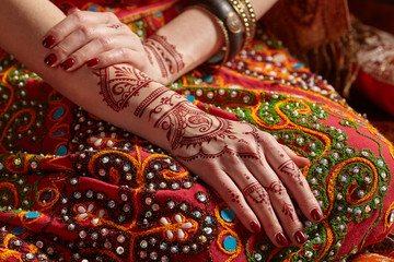 Mehendi on his hands against the backdrop of a national Indian costume. Close-up.