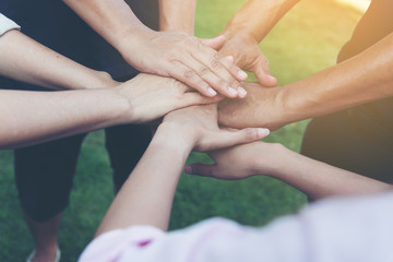 Closeup of stack of hands. Colleague putting their hands on top of each other symbolizing unity and teamwork while doing activity outdoor. People joining hand together as a business goal achievement.