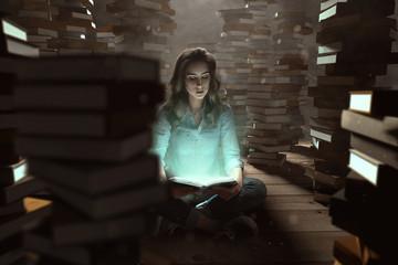 Frau liest zwischen Bücherstapeln