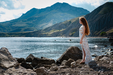 Beautiful boho styled model wearing white dress posing on the beach in sunlight