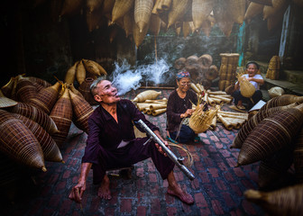 Vietnamese fishermen are smoking and doing basketry for fishing equipment at morning in Thu Sy Village, Vietnam.