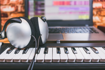 headphone on midi keyboard, computer music. home studio concept