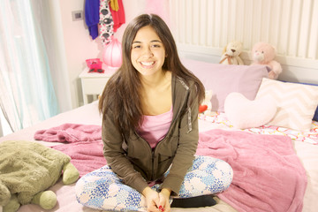 Cute hispanic teenager smiling sitting in bed
