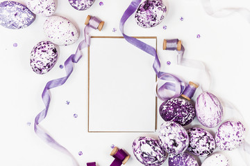 Easter composition with purple marble eggs, sequins and silk ribbons on a white background. Space for a greeting text. Easter, spring concept, template cards. Flat lay, top view.