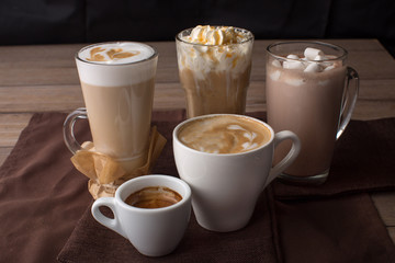 Assortment of coffee drinks in different cups on the table
