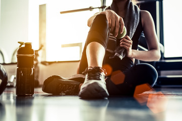 Poster Fitness Sport woman sitting and resting after workout or exercise in fitness gym with protein shake or drinking water on floor. Relax concept. Strength training and Body build up theme. Warm and cool tone