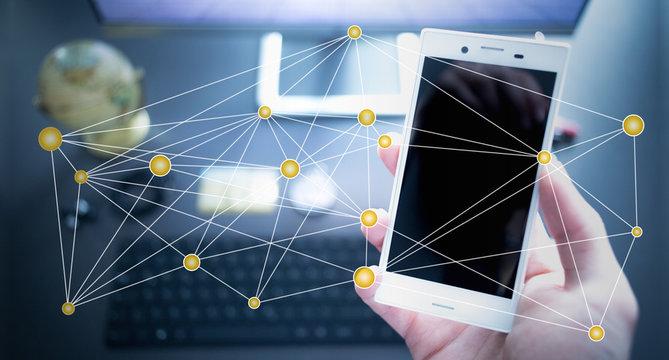 Vernetzung, Smartphone in Männerhand am Arbeitsplatz