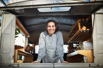 Portrait of smiling mid adult owner standing in food truck