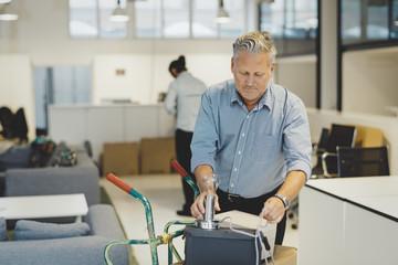 Mature man arranging desk lamp on box in office