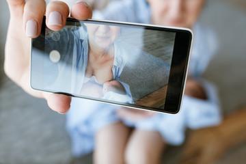 mother breastfeeding mobile photo newborn baby concept. family memories selfie.