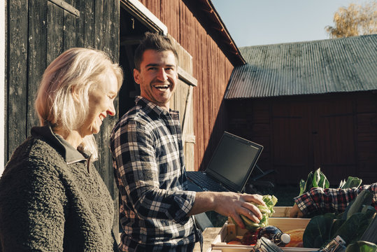 Cheerful male farmer arranging vegetables in crate while standing by friend outside barn