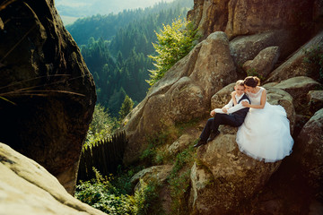 Gorgeous bride is softly hugging the smiling glamour groom back while sitting on the rock at the background of the magnificent landscape of forests.