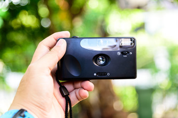 Asian Man hands are holding the camera to shoot or selfie himself. with bokeh
