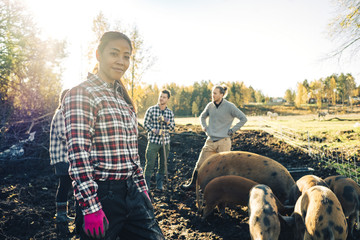 Portrait of mature female farmer with friends and pigs in background at organic farm