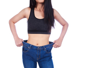 close up of woman show her weight loss and wearing her old jeans isolated on white background